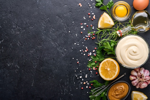 Homemade mayonnaise sauce and ingredients lemon, eggs, olive oil, spices and herbs, black background copy space. food cooking background. top view.