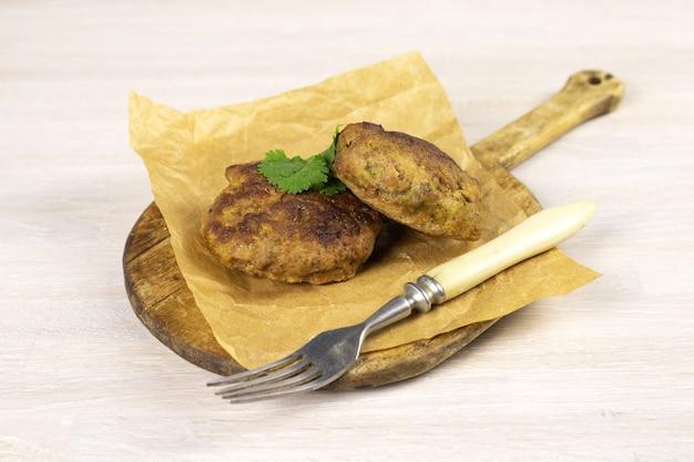 フォークとハーブと白いテーブルのまな板に自家製ミートビーフバーガーパテカツレツ。低炭水化物ダイエットのコンセプト。閉じる。セレクティブフォーカス。コピースペース