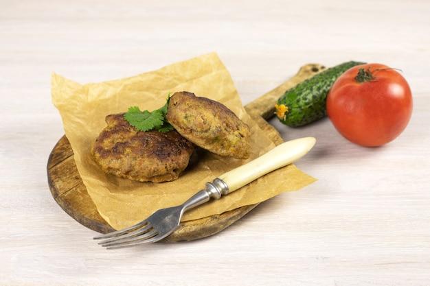 フォーク、野菜、ハーブと白いテーブルのまな板に自家製ミートビーフバーガーパテカツレツ。低炭水化物ダイエットのコンセプト。閉じる。セレクティブフォーカス。コピースペース