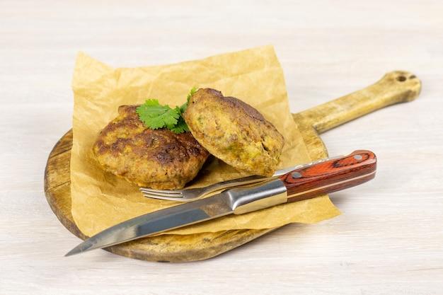 ナイフとハーブで白いテーブルのまな板に自家製ミートビーフバーガーパテカツレツ。低炭水化物ダイエットのコンセプト。閉じる。セレクティブフォーカス。コピースペース