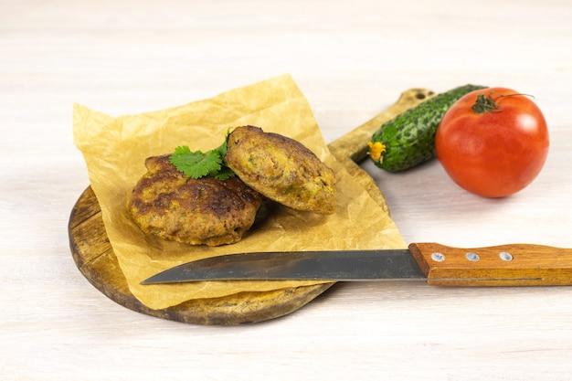 ナイフ、野菜、ハーブと白いテーブルのまな板に自家製ミートビーフバーガーパテカツレツ。低炭水化物ダイエットのコンセプト。閉じる。セレクティブフォーカス。コピースペース