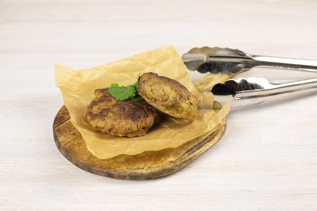 白いテーブルのまな板に肉のトングとハーブを添えた自家製ミートビーフバーガーパテカツレツ。低炭水化物ダイエットのコンセプト。閉じる。セレクティブフォーカス。コピースペース