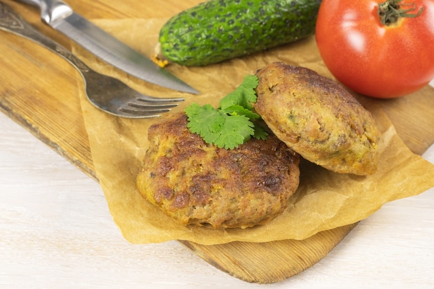 野菜、フォーク、ナイフと白いテーブルのまな板に自家製ミートビーフバーガーパテカツレツ。低炭水化物ダイエットのコンセプト。閉じる。セレクティブフォーカス。コピースペース