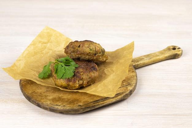 野菜、フォーク、ナイフ、塩、コショウ、ハーブと白いテーブルのまな板に自家製ミートビーフバーガーパテカツレツ。低炭水化物ダイエットのコンセプト。閉じる。セレクティブフォーカス。コピースペース