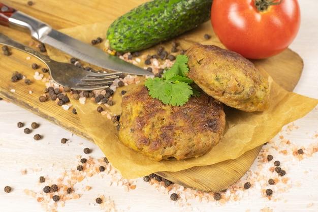 野菜、フォーク、ナイフ、塩、コショウと白いテーブルのまな板に自家製ミートビーフバーガーパテカツレツ。低炭水化物ダイエットのコンセプト。閉じる。セレクティブフォーカス。コピースペース