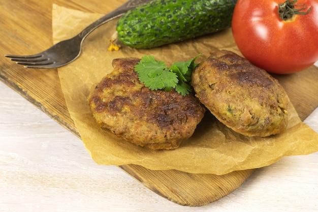 野菜、フォークと白いテーブルのまな板に自家製ミートビーフバーガーパテカツレツ。低炭水化物ダイエットのコンセプト。閉じる。セレクティブフォーカス。コピースペース