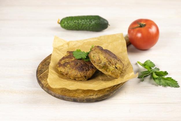 まな板の上に自家製ミートビーフバーガーパテカツレツ、野菜、ハーブと白いテーブルの上に紙を焼く。低炭水化物ダイエットのコンセプト。閉じる。セレクティブフォーカス。コピースペース