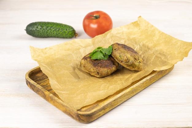 木製トレイに自家製ミートビーフバーガーパテカツレツ、野菜、ハーブと白いテーブルにベーキングペーパー。低炭水化物ダイエットのコンセプト。閉じる。セレクティブフォーカス。コピースペース