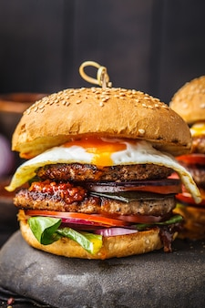 Homemade meat burger with egg, sauce and vegetables on dark background.