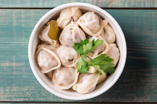 Homemade meat dumplings russian pelmeni with parsley in plate close up.