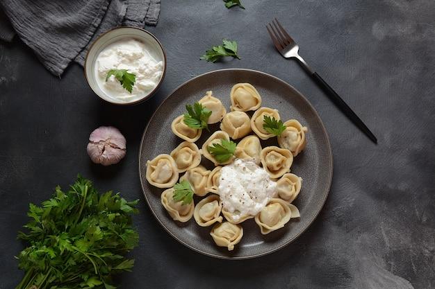 自家製の肉団子にサワークリームと新鮮なパセリを添えて。 (ロシアのペリメニ)