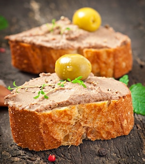 Homemade meat snack chicken liver pate with savory and olives