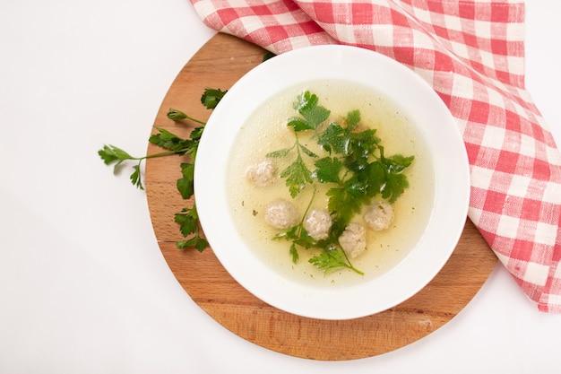 Домашний суп из фрикаделек с овощами в белой тарелке.