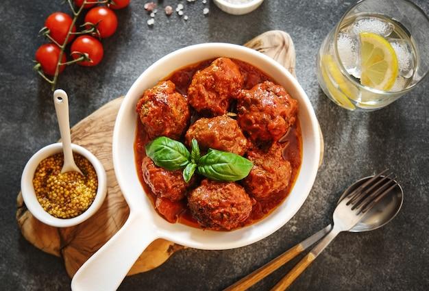 トマトソースとスパイスを添えた自家製ミートボールを灰色の背景に白い鍋でお召し上がりいただけます。上面図。フラットレイ。