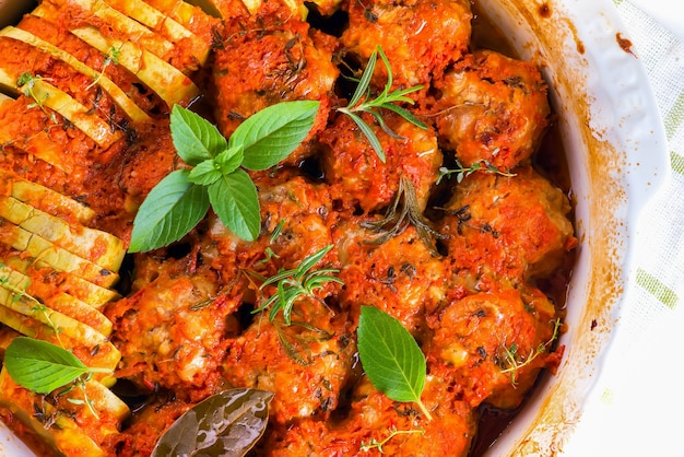 Homemade meatballs with tomato sauce in a white dish baked in the oven with herbs close up