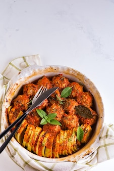 Homemade meatballs with tomato sauce in a white dish baked in the oven with herbs on marble surface