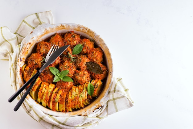 Homemade meatballs with tomato sauce in a white dish baked in the oven with herbs on marble white surface