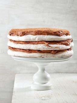 흰색 나무 테이블에 초콜릿 크림을 곁들인 홈메이드 머랭과 너트 케이크