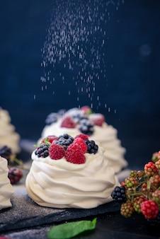 Домашняя безе основа для торта павлова со свежей черникой и blackberry и сахарной пудрой на черном бетоне
