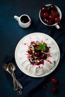 自家製メレンゲケーキパブロバ、ホイップクリーム、フレッシュチェリー、ダークコンクリートのソース添え