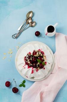 自家製メレンゲケーキパブロバ、ホイップクリーム、フレッシュチェリー、軽いコンクリートのソース