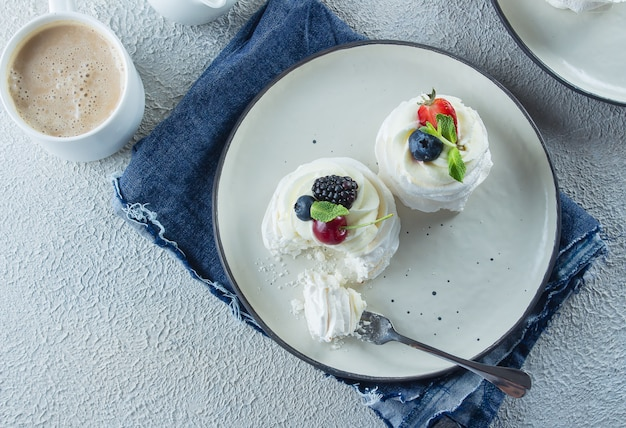 Homemade meringue dessert pavlova cake with fresh berries, cup of coffee latte.