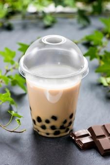 Самодельный чай с пузырьками молока и жемчуг тапиоки в пластиковой чашке с шоколадом на столе.