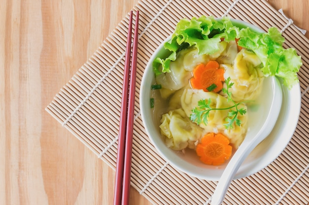 Homemade minced pork and shrimp wonton soup in white bowl on wood table in top view flat l