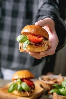 Домашние мини-бургеры с тушеной говядиной в руках