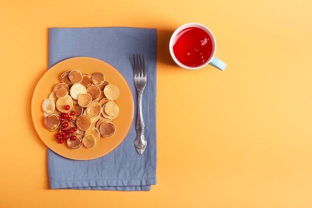 青いナプキンの上にオレンジプレートの自家製ミニパンケーキが立っています