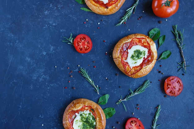 Homemade mini pizza with tomatoes, cheese and bacon, injuries and spices.