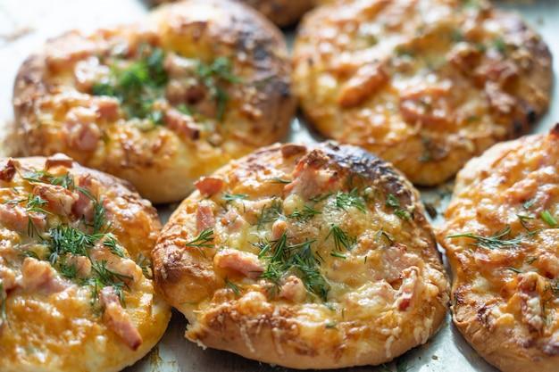 Домашняя мини-пицца, запеченная с начинкой из сырной ветчины и зелени на противне.