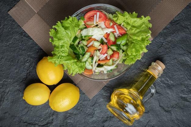 黒の背景に昼食のためのテーブルの上の自家製ミックスサラダ。高品質の写真