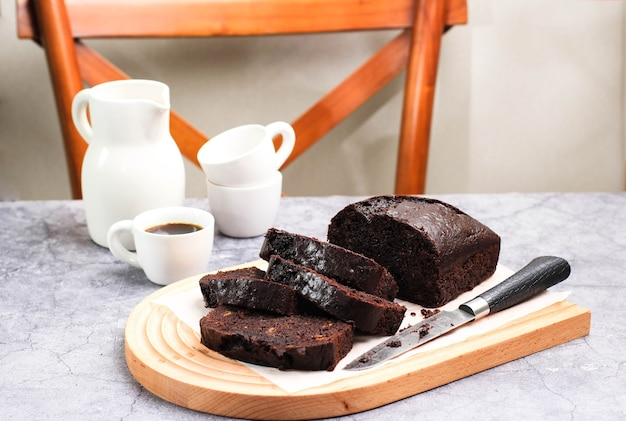 Homemade moist loaf chocolate banana cake brownies served with a cup of coffee.