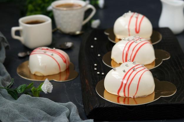 Домашние муссовые пирожные сердечки с белой зеркальной глазурью на темном фоне