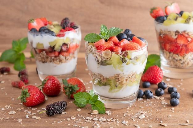 自家製ミューズリー、オーツ麦のグラノーラ ボウル、ヨーグルト、新鮮なブルーベリー、桑、イチゴ、キウイ、ミント、ナッツのボードで健康的な朝食、コピー用スペース。健康的な朝食のコンセプト。きれいに食べる。