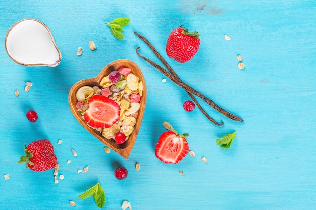 ナッツ、砂糖漬けの果物、青いテーブルの上のハート型の木製のボウルに果実の自家製ミューズリー。