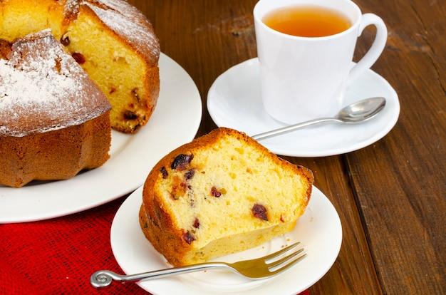 Домашний кекс с сушеными ягодами и сахарной пудрой на тарелке