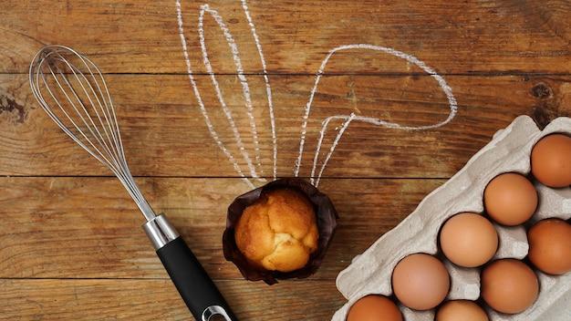 ウサギの耳が描かれた自家製マフィン。木製の表面にマフィン、ウィスク、卵