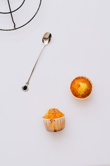 Homemade muffins on a white background and silver spoon