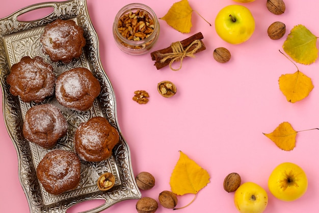 Homemade muffins with apples and nuts arranged on a tray on a pink background, top view, horizontal, copy space