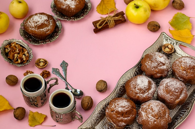 Homemade muffins with apples and nuts and two cups of coffee arranged on a pink , top view, copy space, autumn composition, horizontal orientation