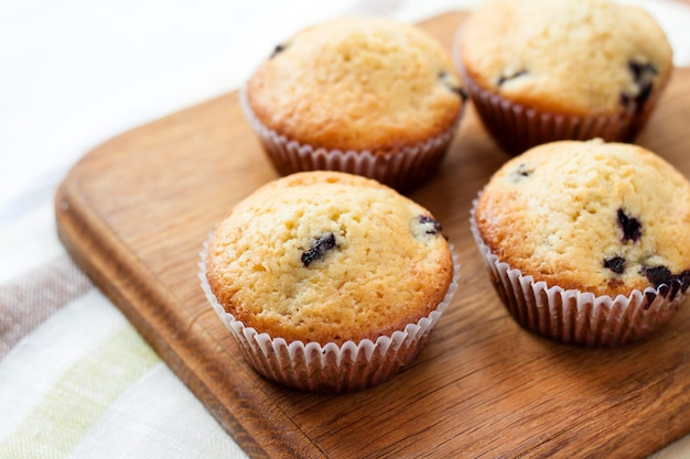Homemade muffins with blueberries on a wooden board
