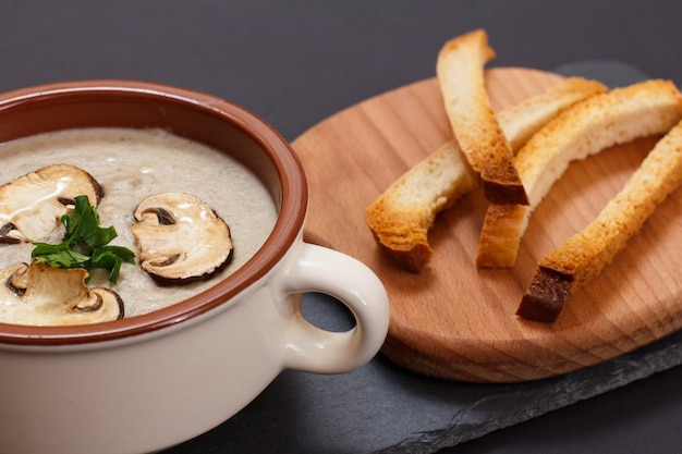 Homemade mushroom cream soup with sliced mushrooms in porcelain bowl, toasts on wooden board in black background. top view.