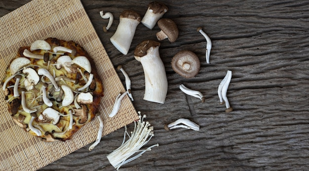 Homemade mushroom pizza on a wooden table background