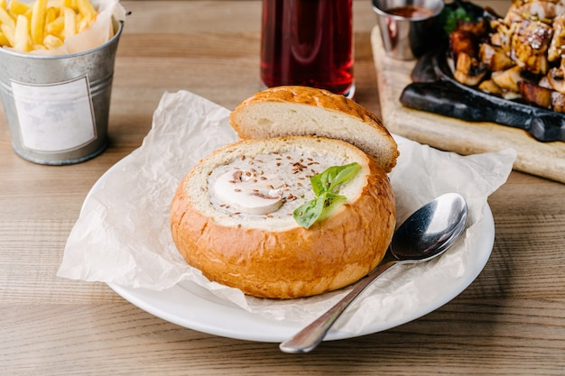 カフェのテーブルの上のブレッドボウルに自家製マッシュルームスープ