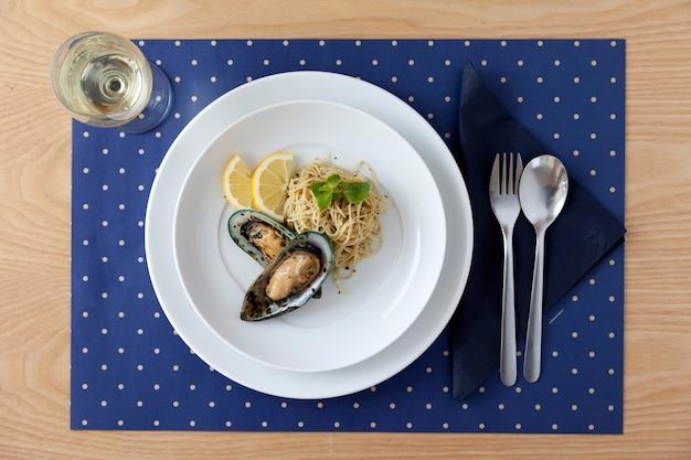 木製のテーブルに白ワインと自家製ムール貝のパスタ料理
