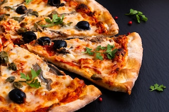 Homemade Napoli Pizza or anchovies pizza on black slate stone