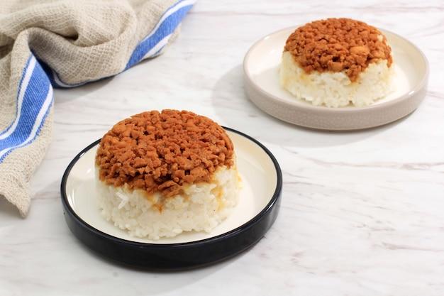 自家製ナシティムアヤム、さいの目に切ったチキン醤油とご飯。朝食のためのインドネシアのコンフォートフード。テキスト用のコピースペースを備えたセラミックプレートで提供