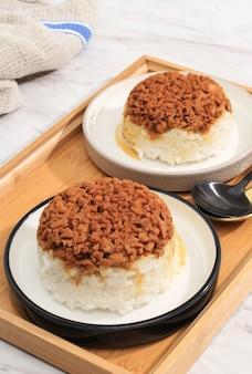 Домашний наси тим аям, рис на пару с куриным соевым соусом, нарезанный кубиками. индонезийская комфортная еда на завтрак. подается на керамической тарелке